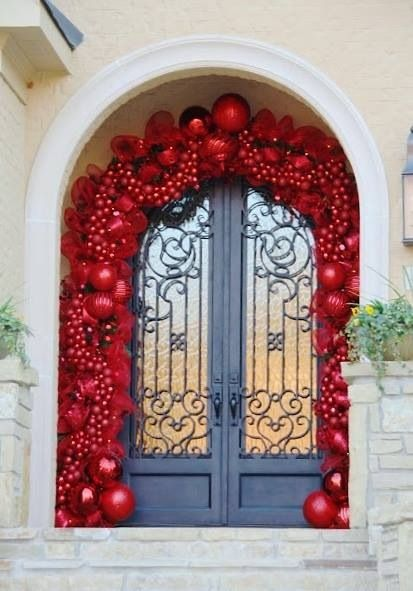 Glamorous red ornaments and ribbon garland on front door.