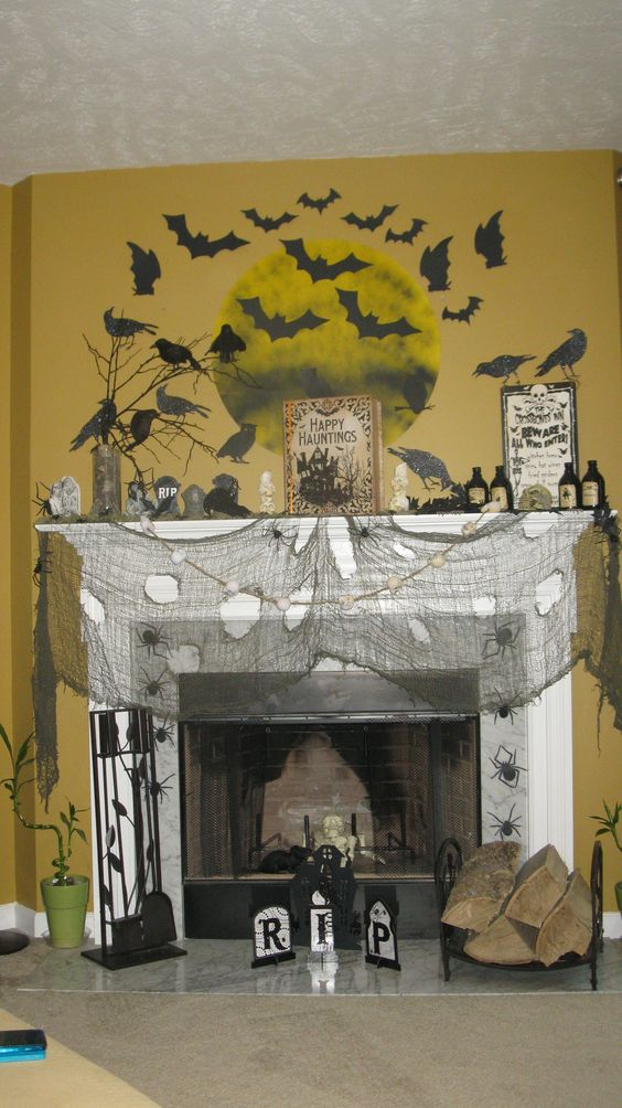 Graveyard mantel decor with bats and full moon.