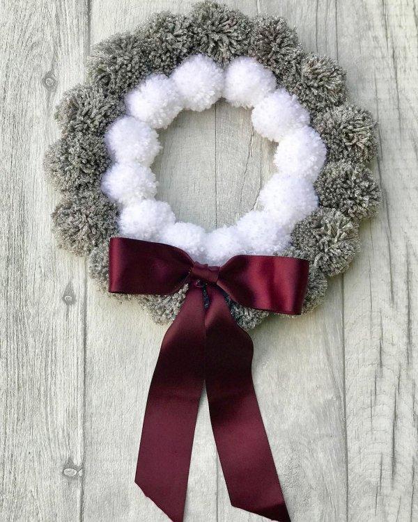 Handmade grey and white pom-pom Christmas wreath.