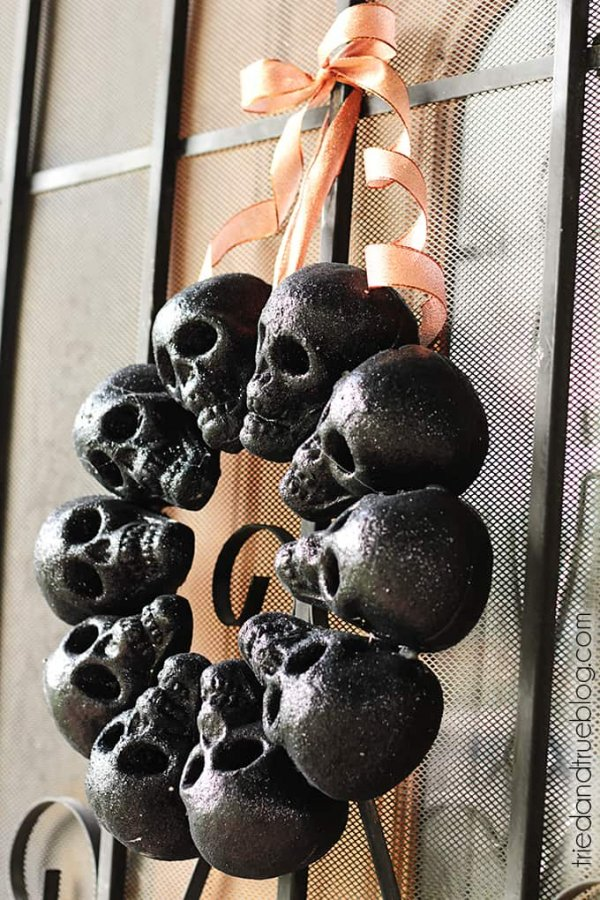 Hang skull wreath with orange ribbon for halloween vibes.