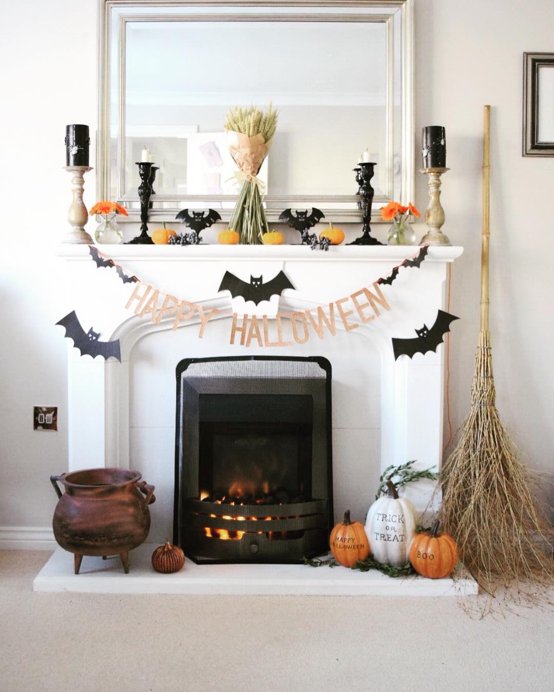 Happy Halloween garland, witch broom, pumpkins, paper bats and candles all used to decorate the Mantel for Halloween party.