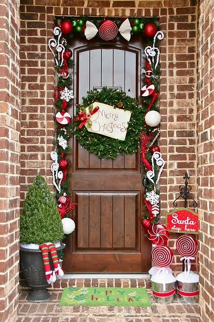 Impressive candy theme porch decoration with small Christmas tree and garland.