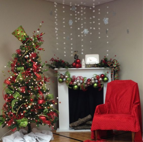 Lovely snowflakes hanging over the fireplace, ornament garland, Christmas tree decorated with beautiful ornaments and red chair perfect for photo back-drop.
