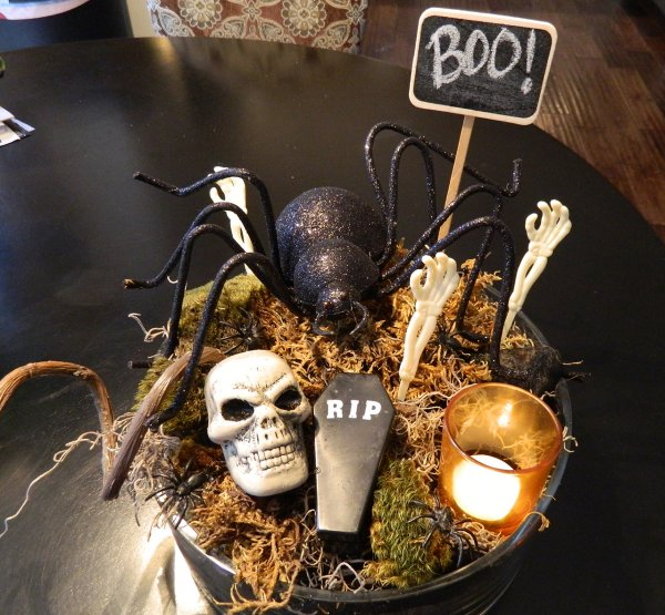 Miniature graveyard on the dining room table with fall foliage, a small coffin, a skull, and spiders.