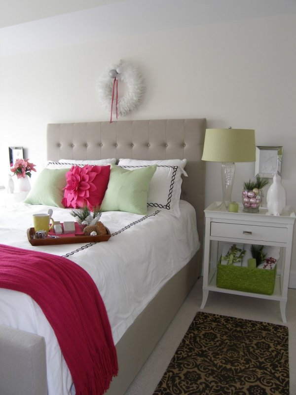 Modish bedroom decor with white feathery wreath, pink and silver ornaments in a jar an magenta pillow cover.