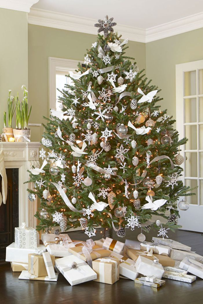 Monochromic Christmas tree decoration with paper doves, frosted pinecones and snowflakes.