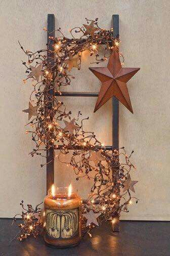 Old ladder is decoreted with dry tree branches, lights and star ornaments.