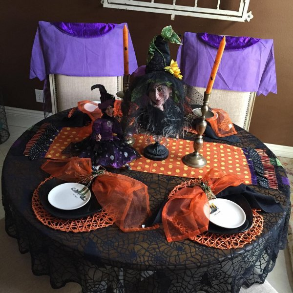Orange and black table decor with witch as centrepiece.