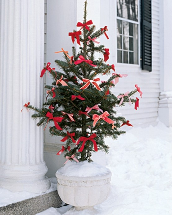 Outdoor Christmas tree decor with red ribbon and white vase.