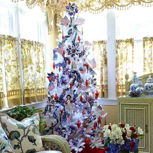Patriotic white tree decorated with red ornaments and flags.