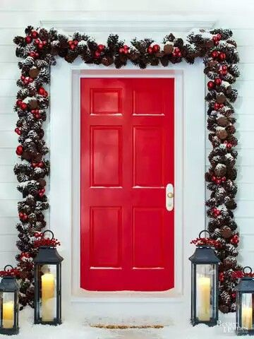 Pinecone garland, red door with lamp on porch.