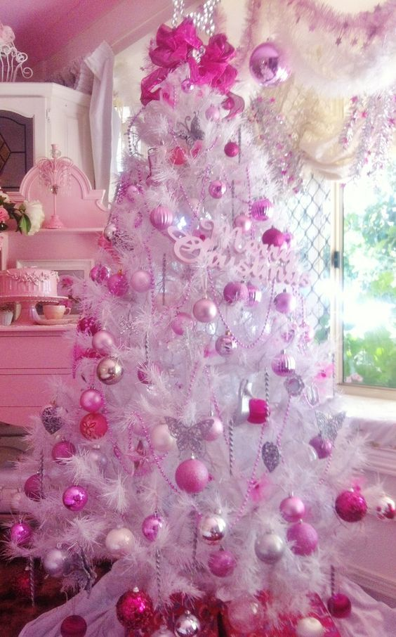 Pink and purple balls hanging on white Christmas tree.