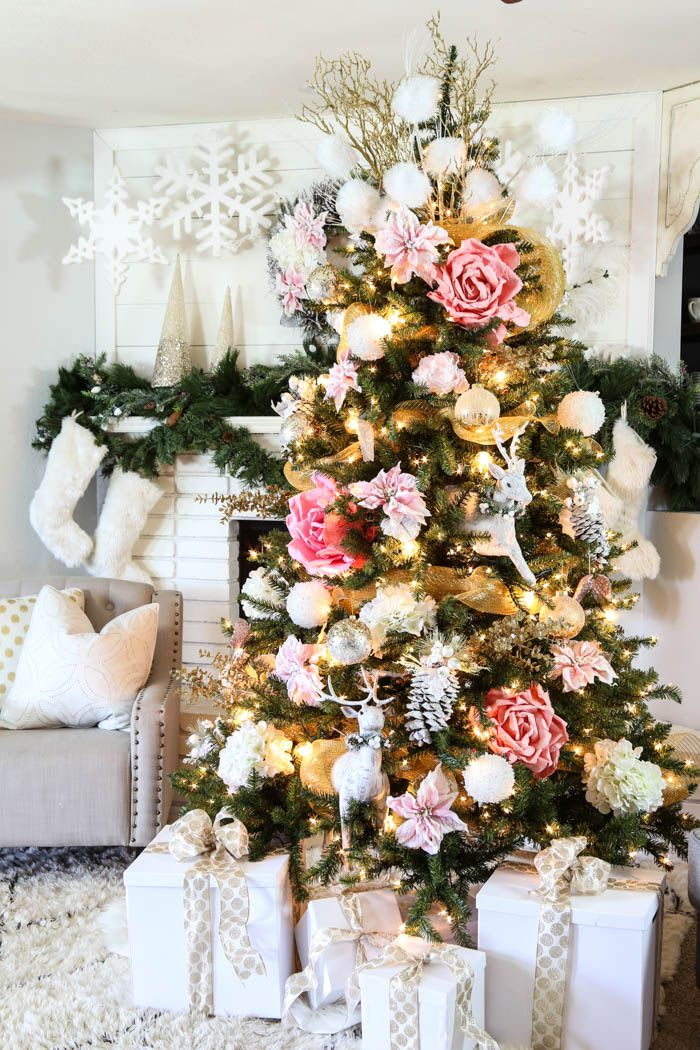 Pink flowers with golden ornaments on Christmas tree.