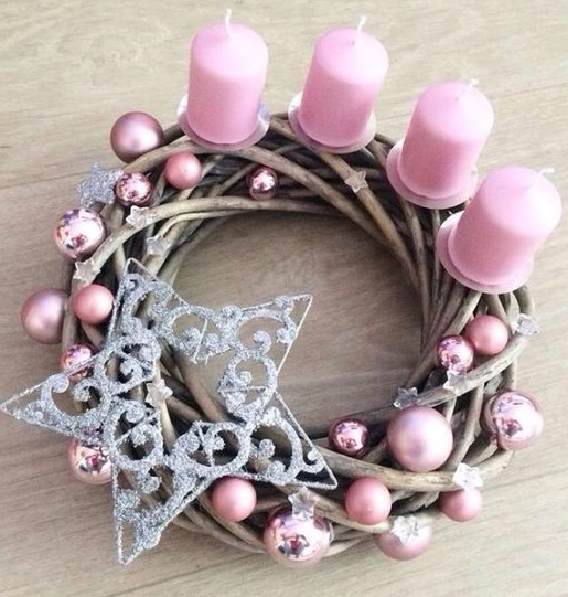 Pretty pink candles in twig branches basket decorated with ornaments and snowflakes.