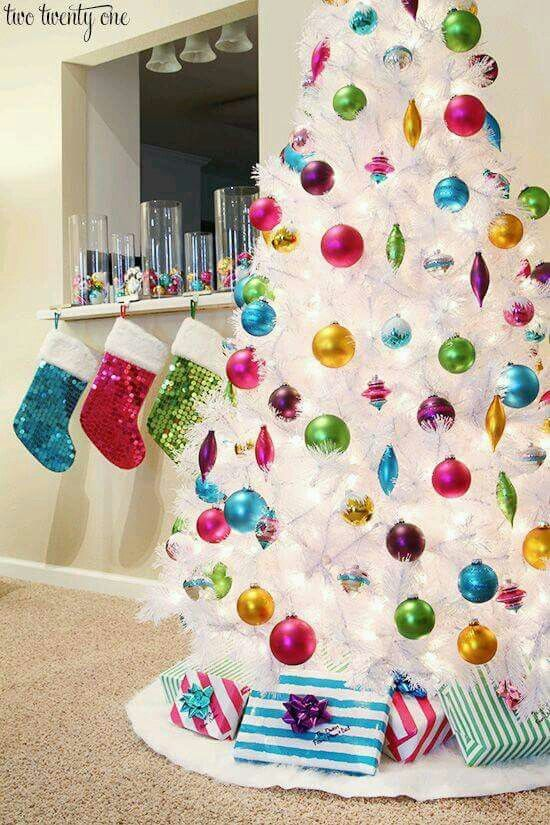 Pure white Christmas tree with colorful ornaments and glittery stockings.
