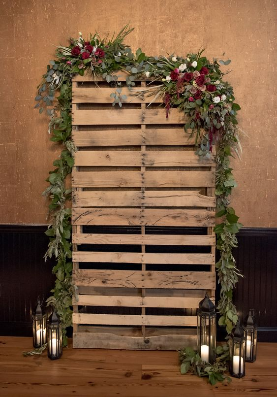 Reclaimed pallet booth decorated with fresh leaves and flowers.