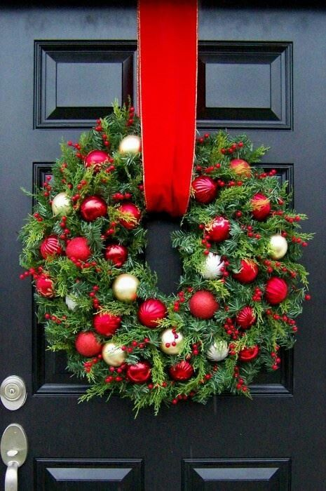 Red and golden ornaments hanging with red ribbon on front door.