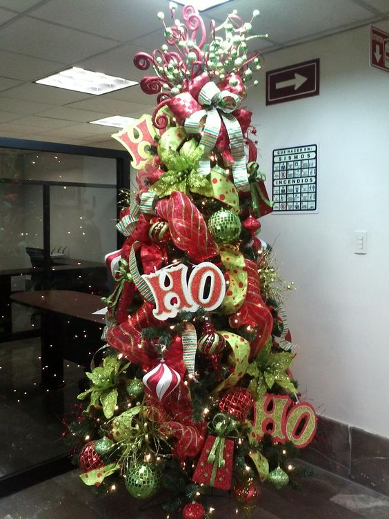 Red and green Christmas tree decor with ribbons and big ornaments.