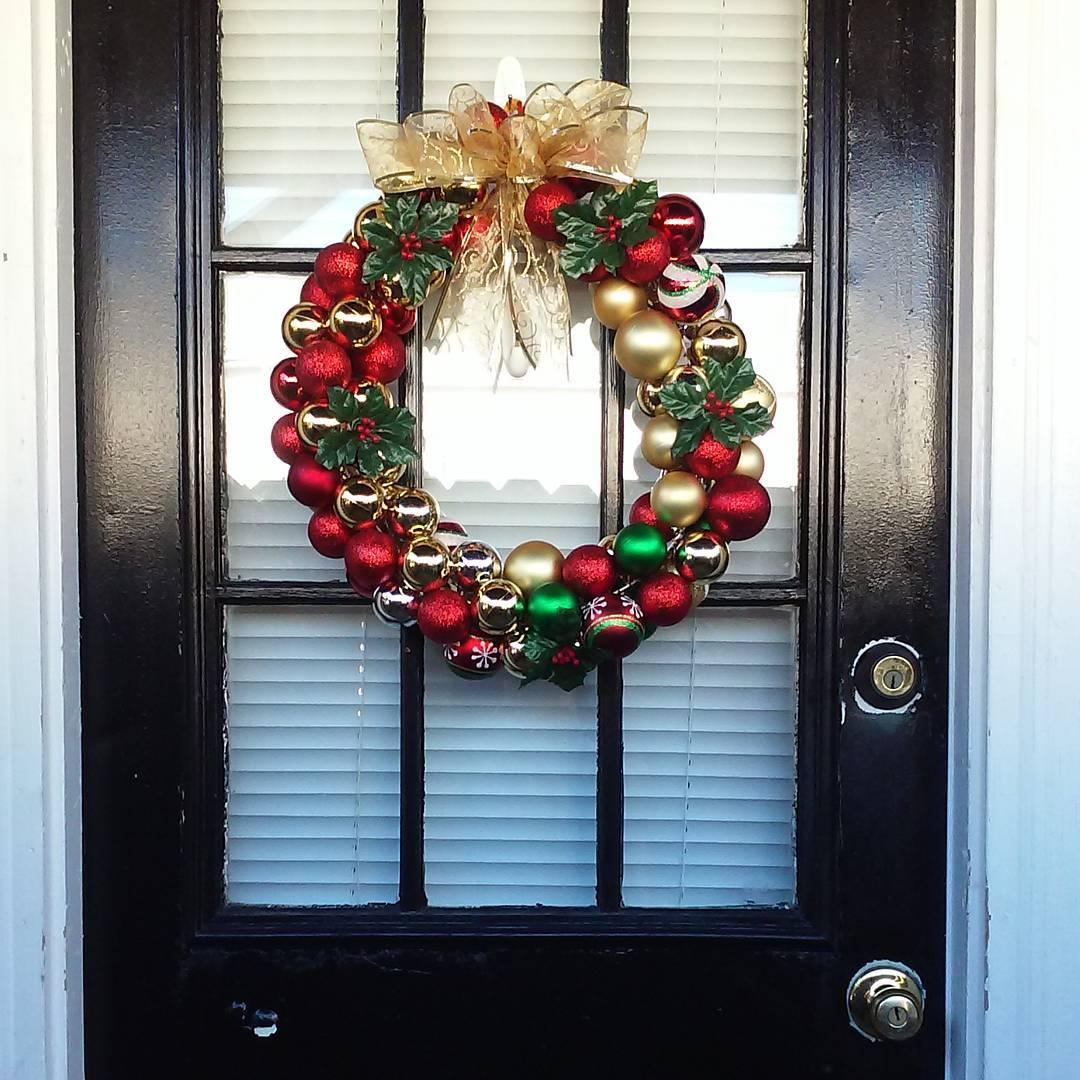 Red, green and golden ornament door wreath with golden bowtie.