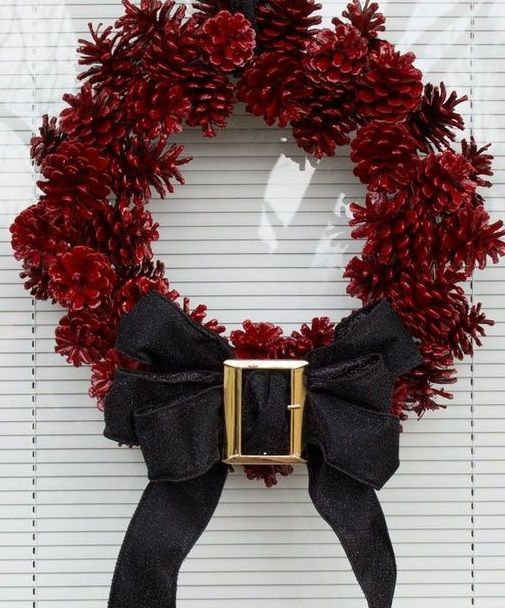 Red pinecone wreath with black belt.