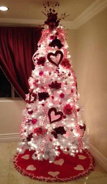 Romantic white X mas tree brightened with lights and heart shape ornaments.
