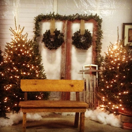 Rustic back-drop with Christmas tree and wreaths decorated with lights.
