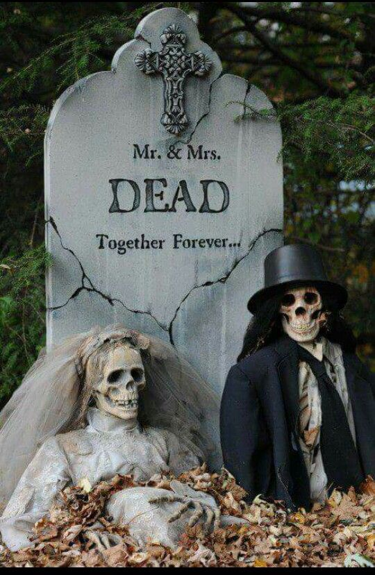 Skeleton couple Graveyard in backyard for Halloween party decoration.
