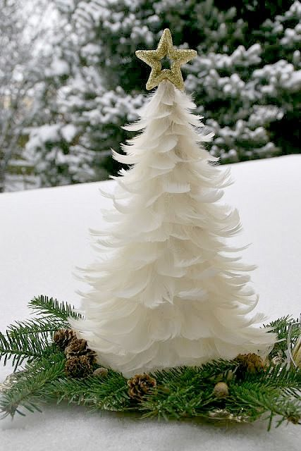 Small milky white Christmas tree with golden star tree topper.