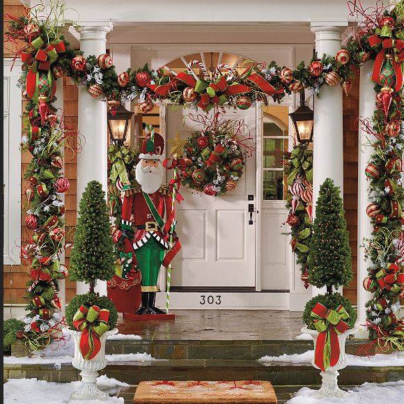 Small trees, garland and wreath with colored ornaments and Santa is standing outside fot porch decoration.