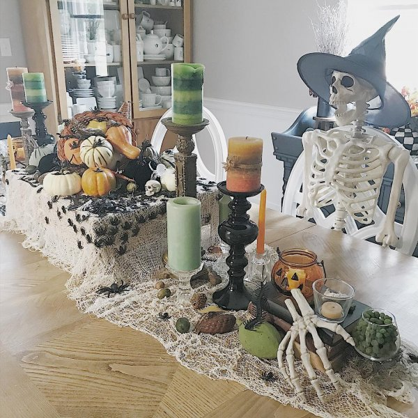 Spiderweb runner, pumpkins, a lot of spiders with skeleton having witch hat waiting for dinner.