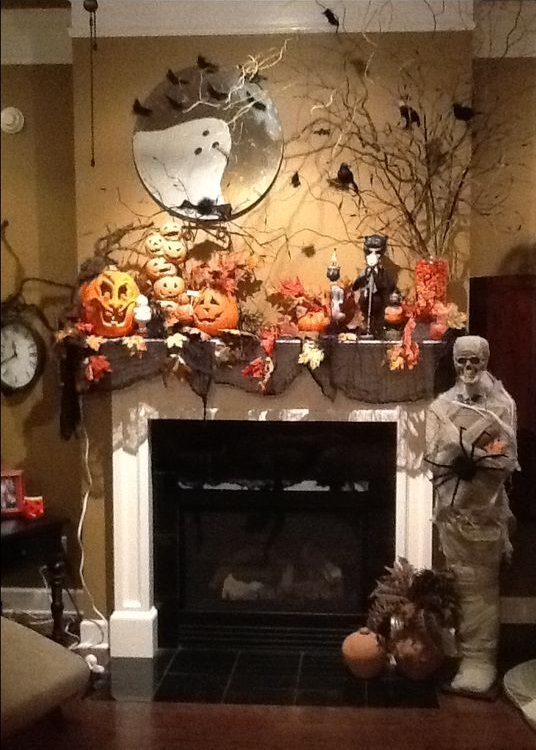 Spooky Halloween mantel decoration with skeleton, spider, crows, pumpkins and tree.