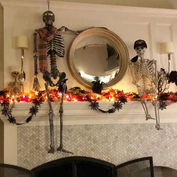 Stylish mantel decor with skeleton and spider web garland.
