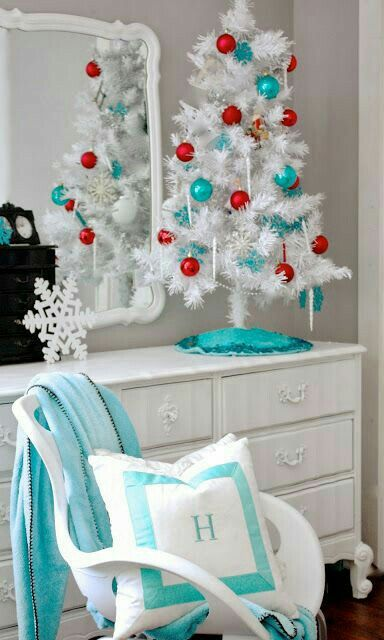 Teal blue and red balls on table top white X mas tree.