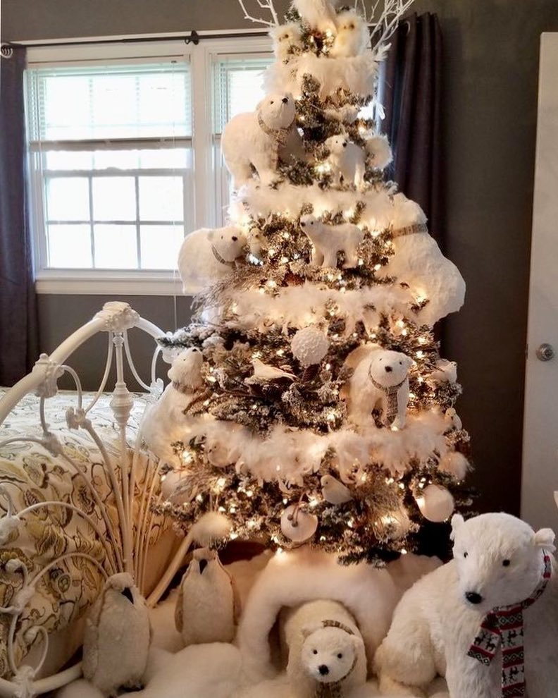 Thick cotton fur wrapped around Christmas tree to give it a white look with bear, balls and birds on it.