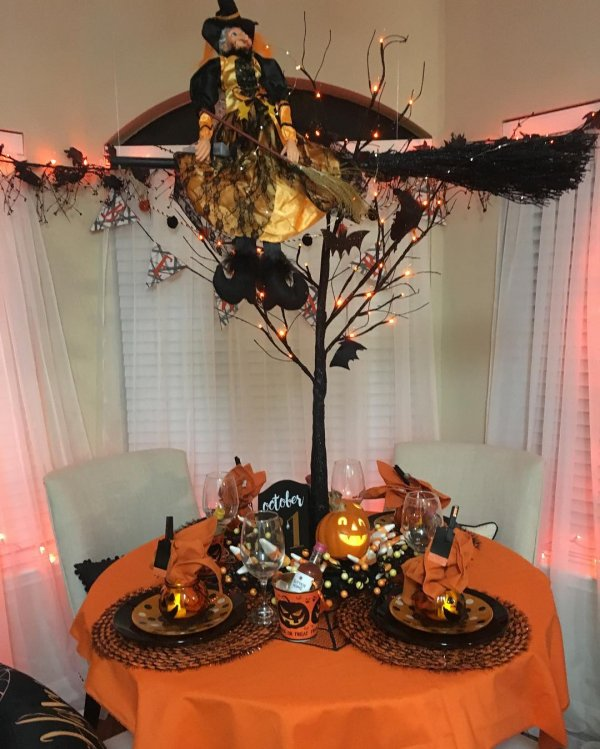 This black Halloween tree decorated with paper bats and lights. Witch is sitting on tree with her broom.
