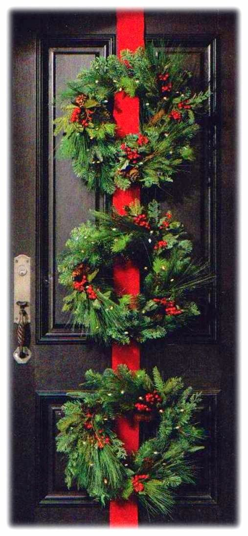 Three green fresh wreath on red ribbon on front door.