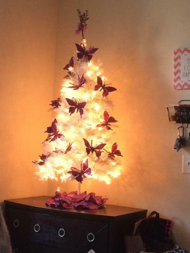 Tissue butterfly on table top white Christmas tree.
