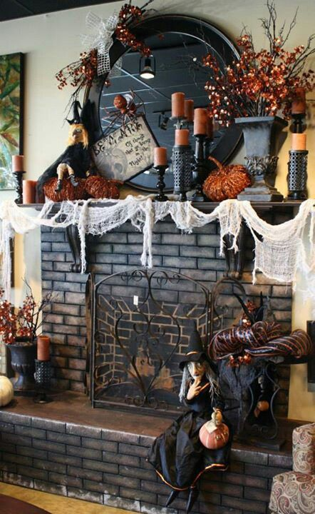 Vintage style Halloween Mantel decor with Witch, cheese cloth as web, candles and lights.