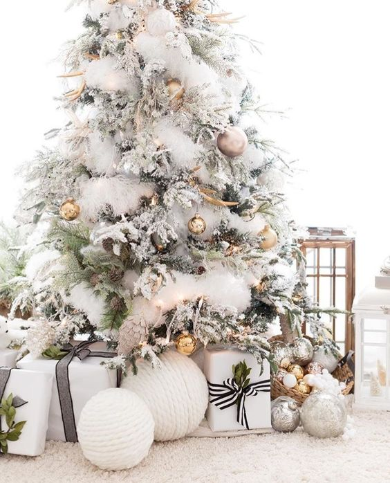 White and golden ornaments On white X Mas tree a perfect blend for unique look.