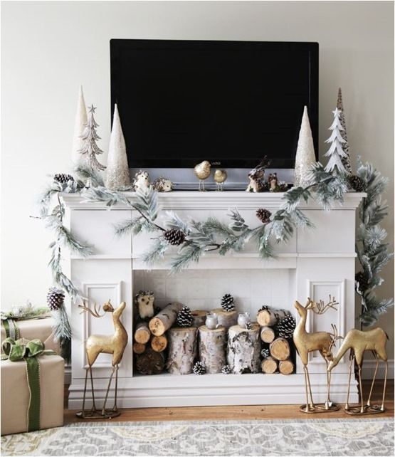 Antique reindeer with artificial tree at mantel.