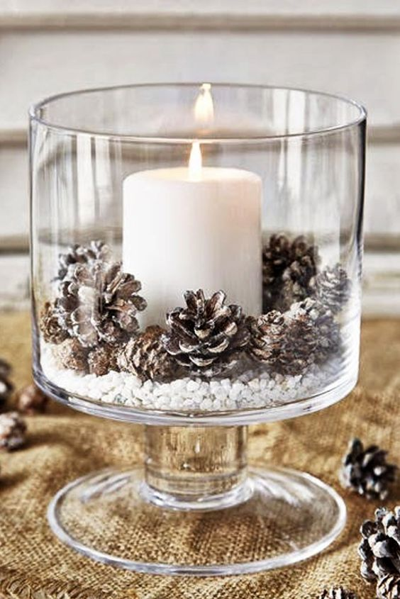 Awesome glass candle holder decorated with pinecones.