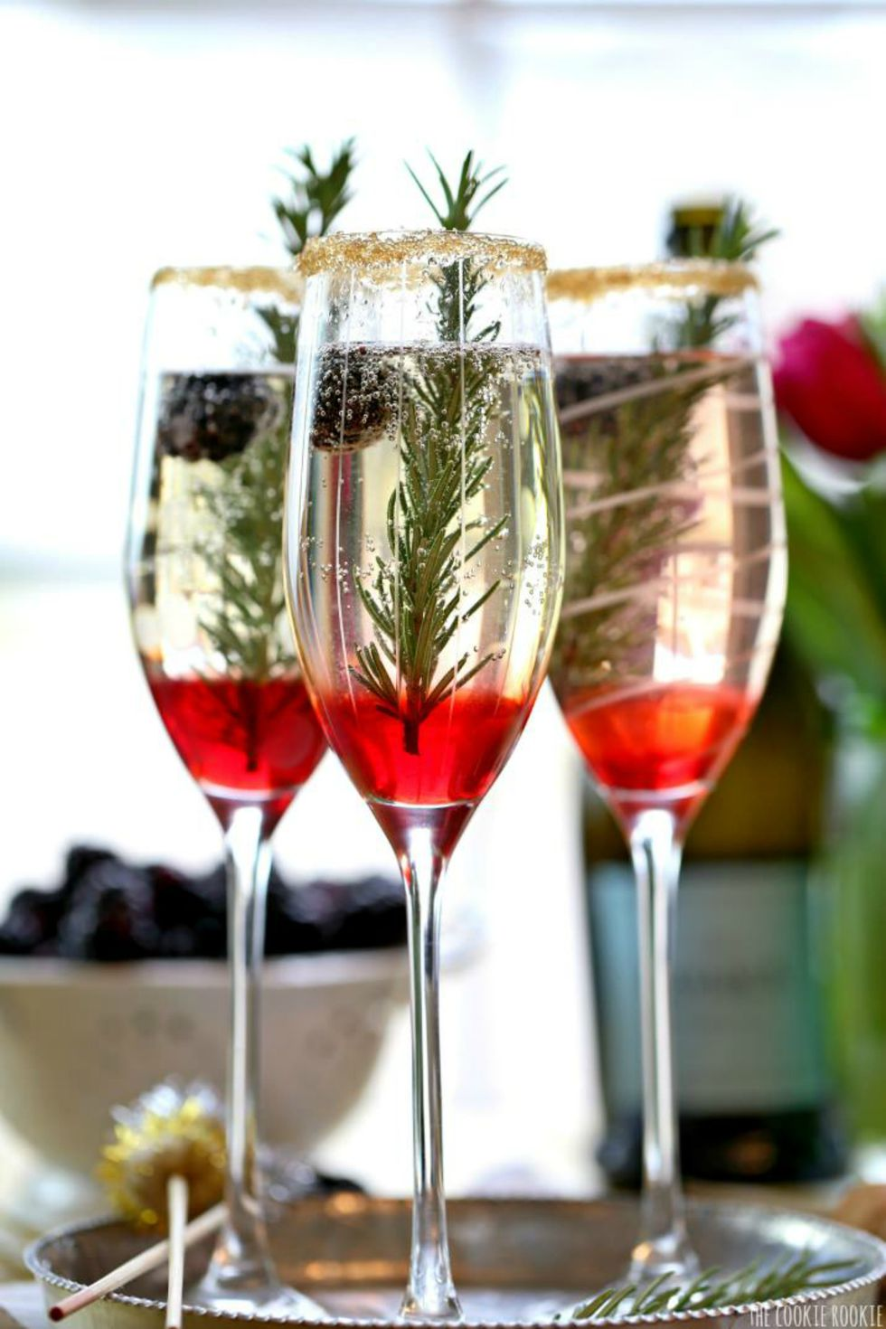 Bubbly champagne cocktail with a fresh sprig of rosemary.