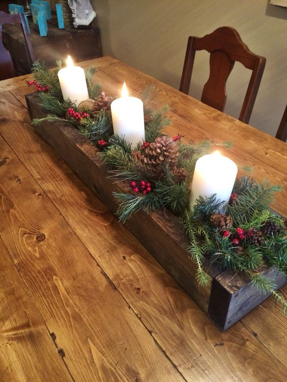 Charming wooden box centerpiece filler with greenery, candles and pinecones.