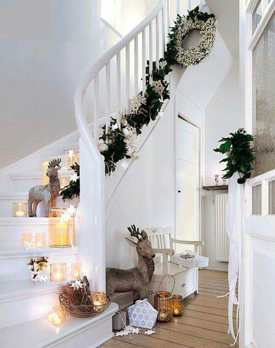 Classic staircase decoration with greenery garland, silver ornaments, candles and floral wreath.