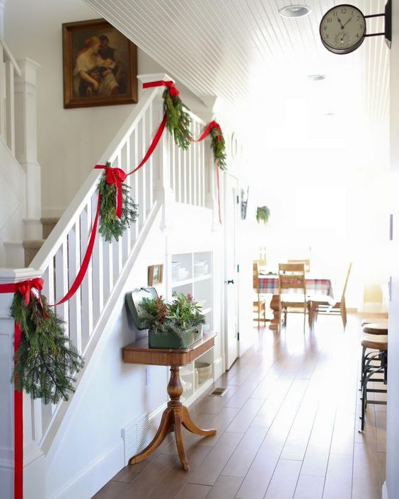 Decorate your staircase with pinecone garland and red ribbon.