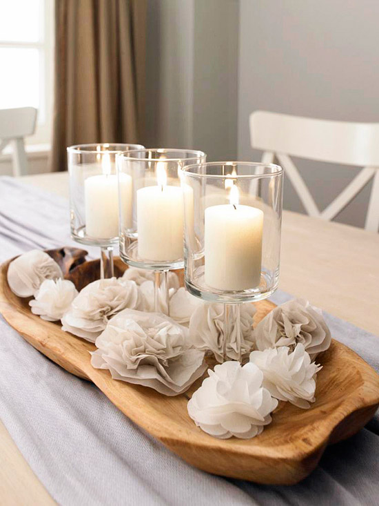 Elegant tissue paper flowers in a tray with candles.
