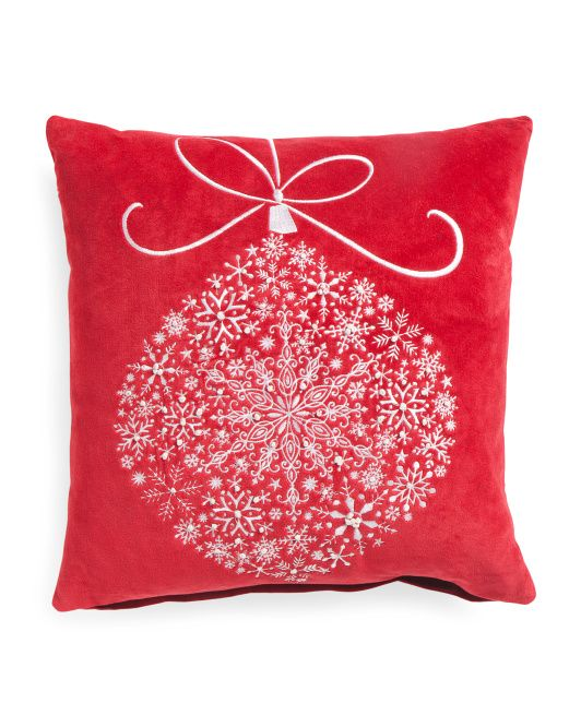 Embroidered ornament on red pillow.