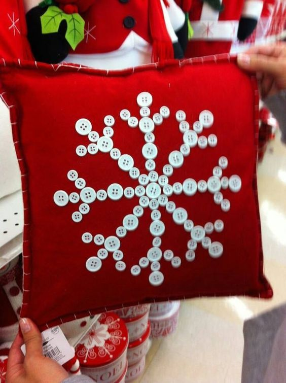 Exclusive button snowflake on red pillow.