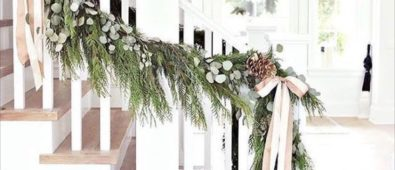 Fresh garland on banister with pinecones and satin ribbon.