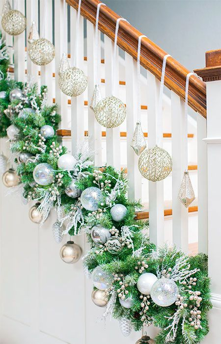 Garland at base of the railing with ornaments anf some balls hanging individully from the banister with ribbon.